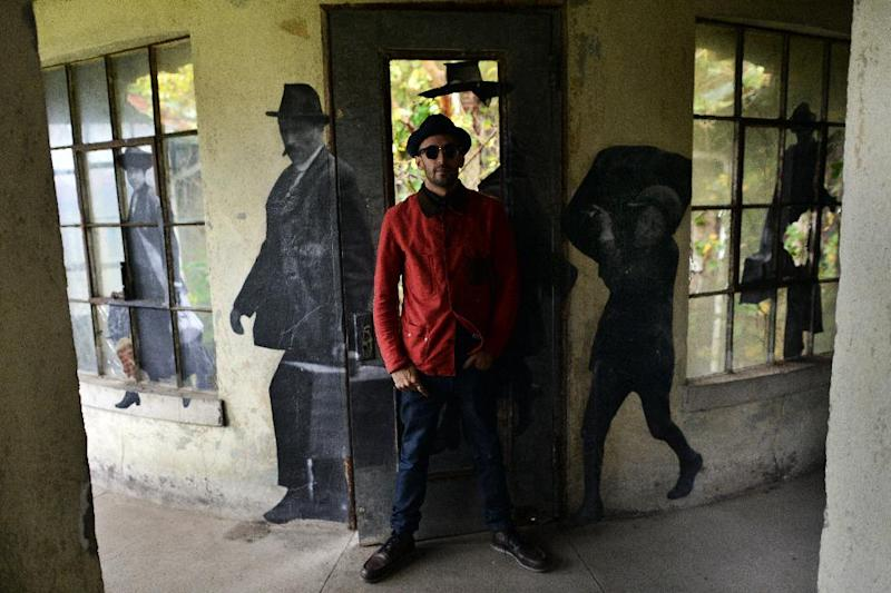 French artist JR stands next to one of his artworks inside the Ellis Island Immigrant Hospital in New York on October 16, 2014 (AFP Photo/Jewel Samad)