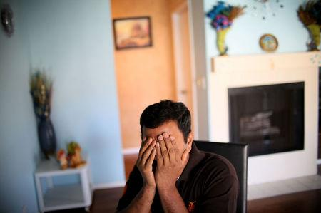 Raj, an immigrant from Sri Lanka, sits in his apartment in San Diego