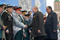 Russian President Vladimir Putin, second from right, and Tajikistan's President Emomali Rakhmon, right, shake hands with WWII veterans before the Victory Day military parade in Moscow, Russia, Sunday, May 9, 2021, marking the 76th anniversary of the end of World War II in Europe. (Alexei Druzhinin, Sputnik, Kremlin Pool Photo via AP)