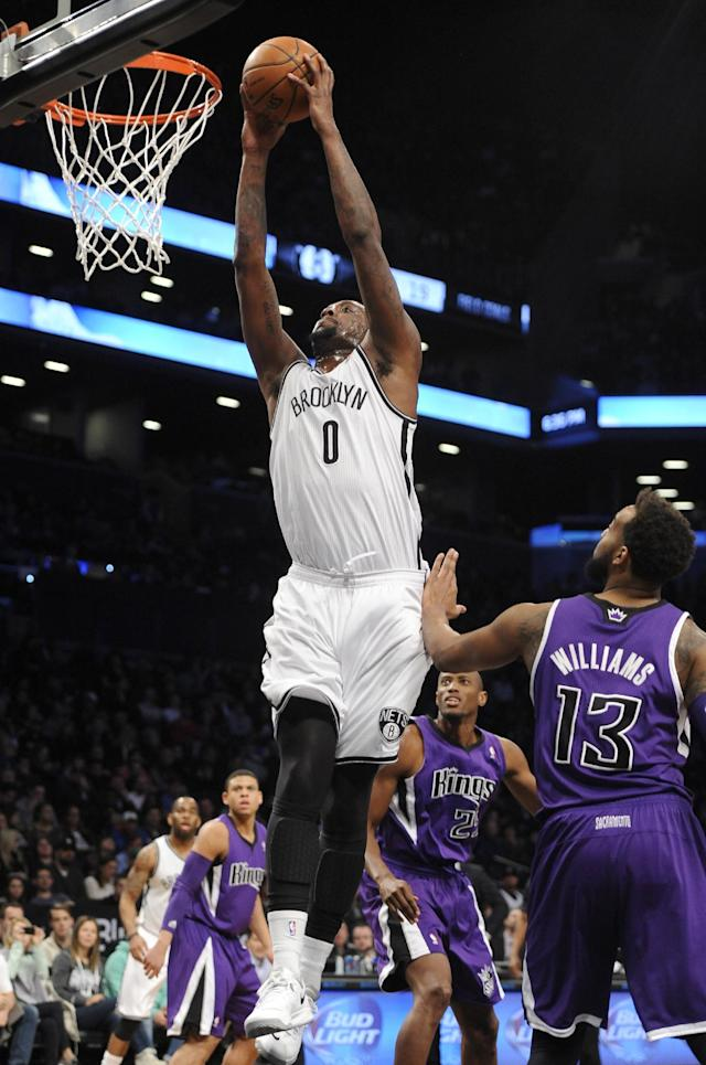 Brooklyn Nets' Andray Blatche (0) drives to the basket past Sacramento Kings' Travis Outlaw (25) and Derrick Williams (13) in the first half of an NBA basketball game on Sunday, March 9, 2014, at Barclays Center in New York. (AP Photo/Kathy Kmonicek)