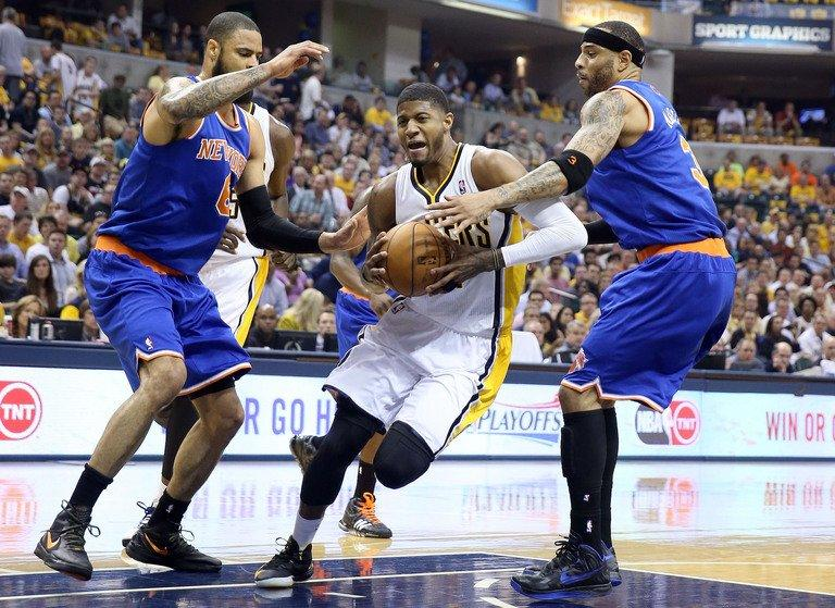 New York Knicks' Tyson Chandler (L) and Kenyon Martin try to block Paul George (C) of the Indiana Pacers on May 14, 2013