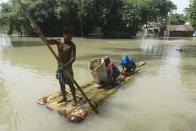 Villager uses a banana tree raft to move across a flooded locality in a flood effected village in Morigaon district of Assam in India on Friday, 17 July 2020. (Photo by David Talukdar/NurPhoto via Getty Images)