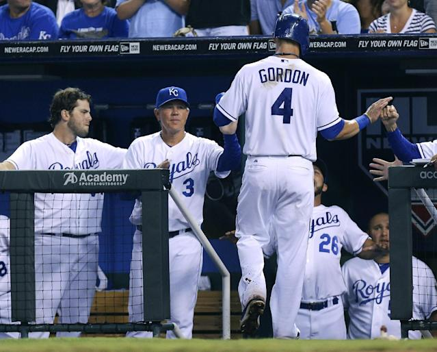Kansas City Royals' Alex Gordon (4) is congratulated by manager Ned Yost (3) and teammates after scoring on an Eric Hosmer single in the fifth inning during a baseball game against the Baltimore Orioles, Thursday, July 25, 2013, in Kansas City, Mo. (AP Photo/Ed Zurga)