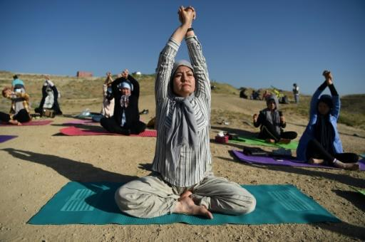 Fakhria Momtaz a teacher and founder of Kabul's first yoga center for women, takes part in a session at Shahrak Haji Nabi hilltop during International Yoga Day
