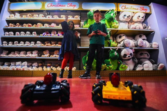 Millie, eight, and Max, nine, play with Laser Battle Hunters during the Hamleys Christmas toy showcase at Hamleys, Regent Street, London