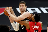 Milwaukee Bucks center Brook Lopez (11) gets tied up by Toronto Raptors guard Kyle Lowry (7) during the second half of an NBA basketball game Wednesday, Jan. 27, 2021, in Tampa, Fla. (AP Photo/Chris O'Meara)