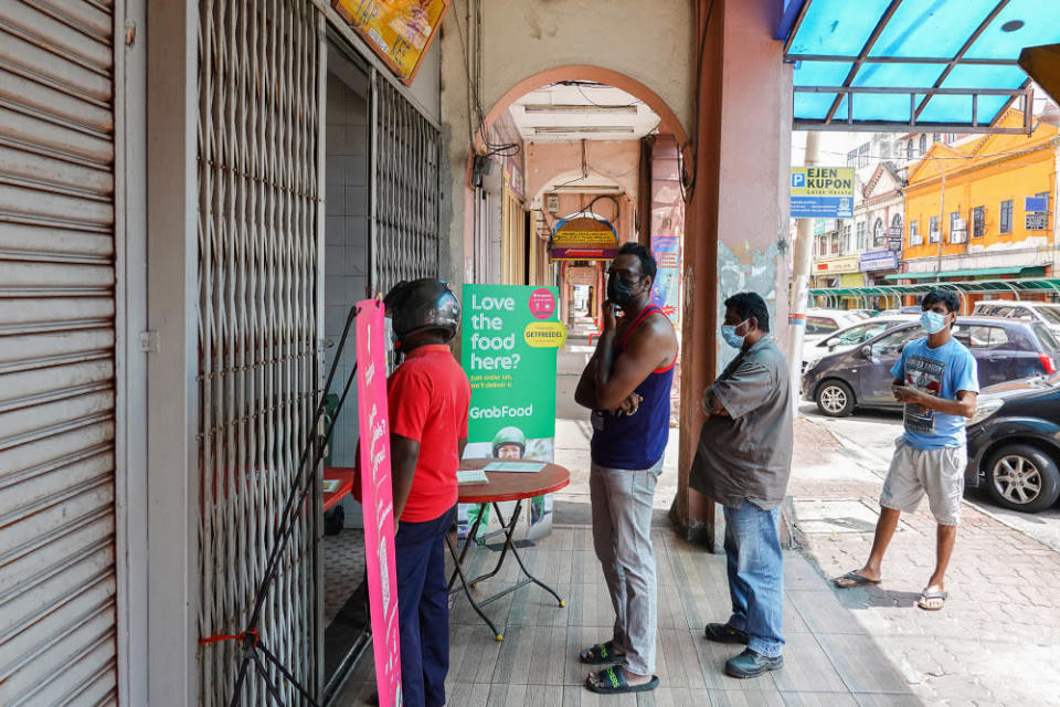Customers queue outside Restaurant Ghuhan for their takeaway banana leaf meal during the movement control order 3.0 (MCO 3.0) in Klang June 23, 2021. — Pictures by Miera Zulyana