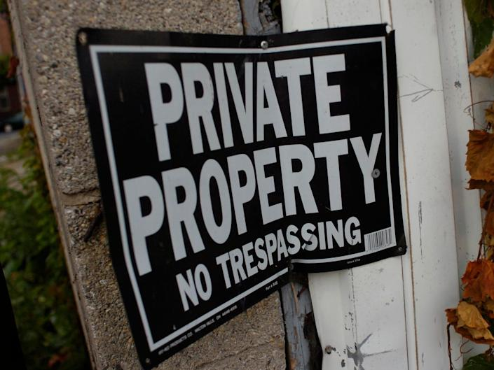 """A black sign with """"private property"""" written in white letters."""