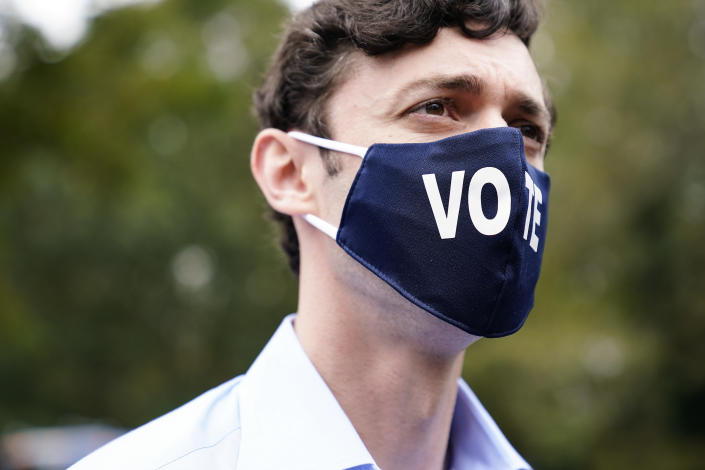 """Democratic candidate for Senate Jon Ossoff watches during a """"Get Out the Early Vote"""" event at the SluttyVegan ATL restaurant on Tuesday, Oct. 27, 2020, in Jonesboro, Ga. (AP Photo/Brynn Anderson)"""