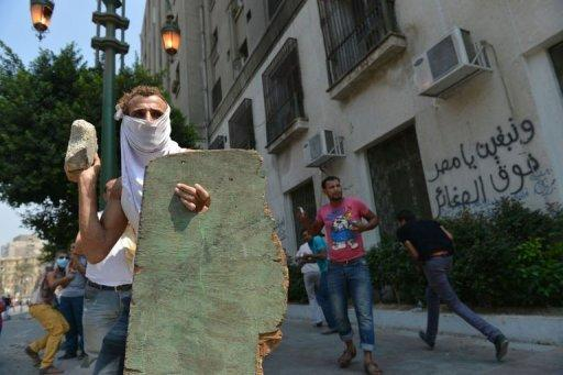 An Egyptian protester holds a makeshift shield as he throws a stone towards the riot police