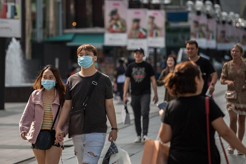 SINGAPORE - 2020/02/14: A couple wearing protective face masks walk along Orchard Road, a famous shopping district in Singapore, on Valentine's Day. Singapore declared the COVID-19 outbreak as Code Orange on February 7, 2020. (Photo by Maverick Asio/SOPA Images/LightRocket via Getty Images)