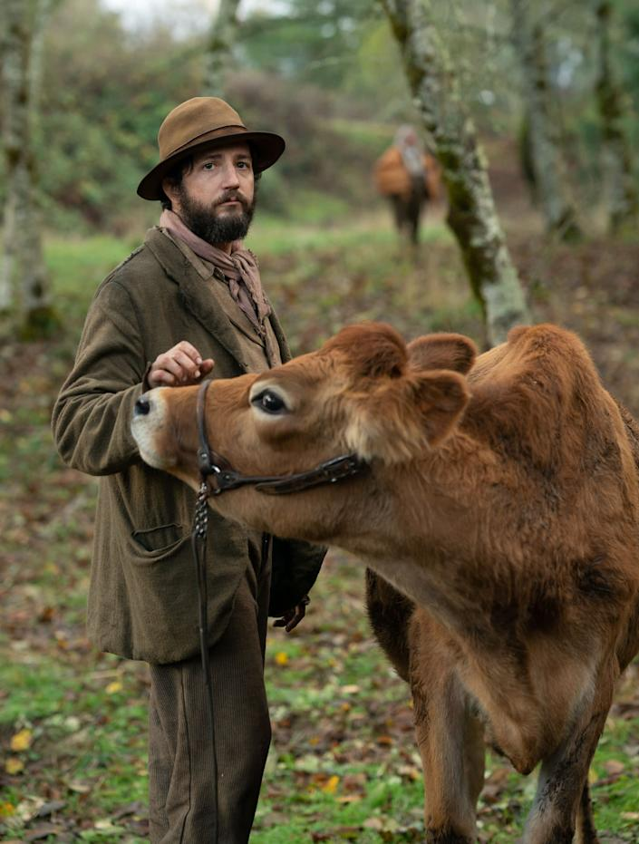 "Eve the cow (seen here with John Magaro) makes her screen debut in ""First Cow."" (Photo: A24)"
