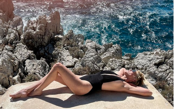 Sharon Stone lying on a rock near the ocean wearing a black plunging swimsuit