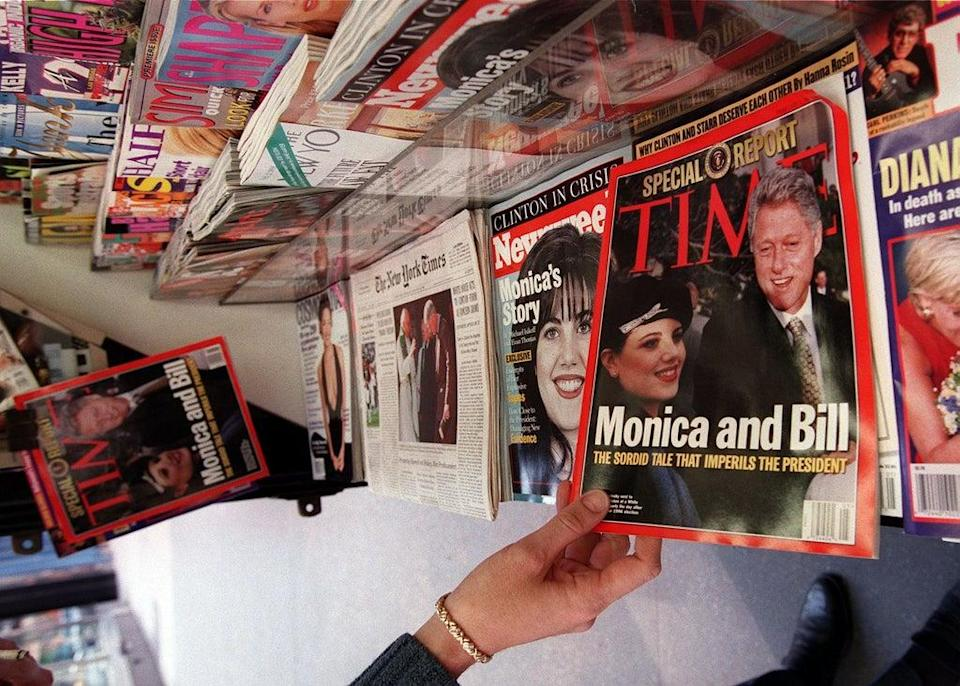 A woman reaches for a copy of Time Magazine on a news stand on 26 January 1998 in New York City (JON LEVY/AFP via Getty Images)
