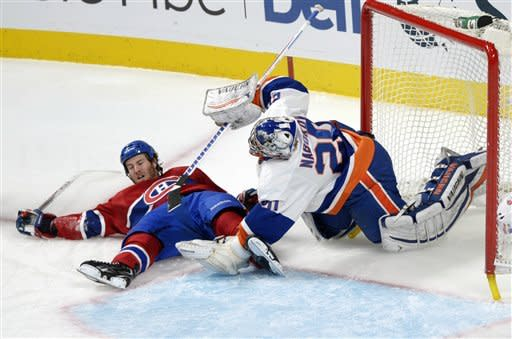 Montreal Canadiens' Brandon Prust, left, collides with New York Islanders goaltender Evgeni Nabokov during the second period of their NHL hockey game, Thursday, Feb. 21, 2013, in Montreal. (AP Photo/The Canadian Press, Graham Hughes)