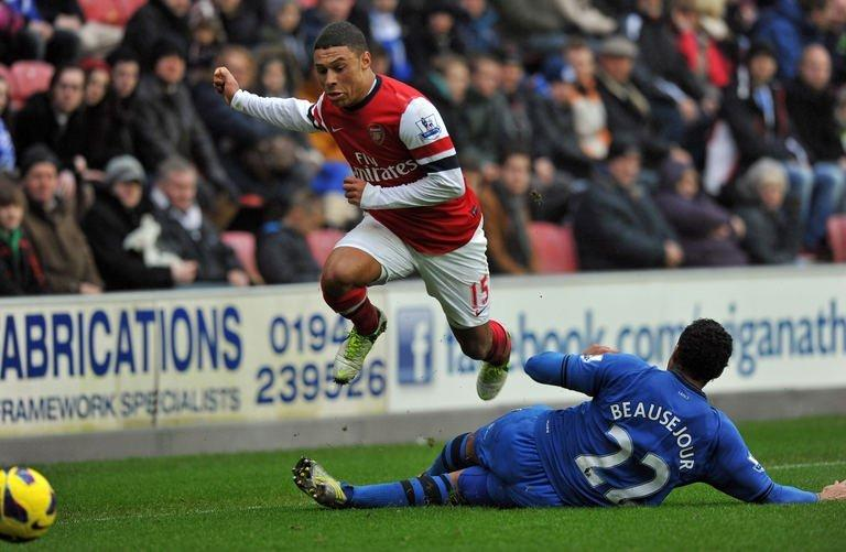 Wigan Athletic's midfielder Jean Beausejour (R) tackles Arsenal's midfielder Alex Oxlade-Chamberlain during their English Premier League football match at The DW Stadium in Wigan, north-west England on December 22, 2012. Arsenal won 1-0