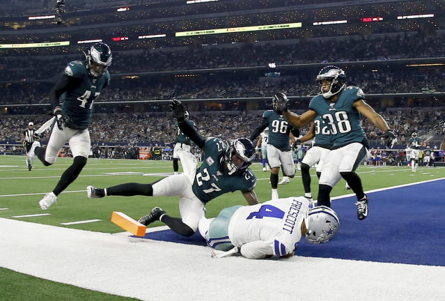 Dallas Cowboys quarterback Dak Prescott (4) reaches the end zone for a touchdown as Philadelphia Eagles' Nate Gerry (47), Malcolm Jenkins (27), and Orlando Scandrick (38) defend in the second half of an NFL football game in Arlington, Texas, Sunday, Oct. 20, 2019. (AP Photo/Ron Jenkins)