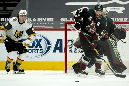 Arizona Coyotes defenseman Alex Goligoski (33) reacts as he watches the puck in front of Coyotes goaltender Darcy Kuemper, right, as Vegas Golden Knights center Cody Glass (9) moves in just prior to his shot for a goal during the third period of an NHL hockey game Friday, Jan. 22, 2021, in Glendale, Ariz. (AP Photo/Ross D. Franklin)