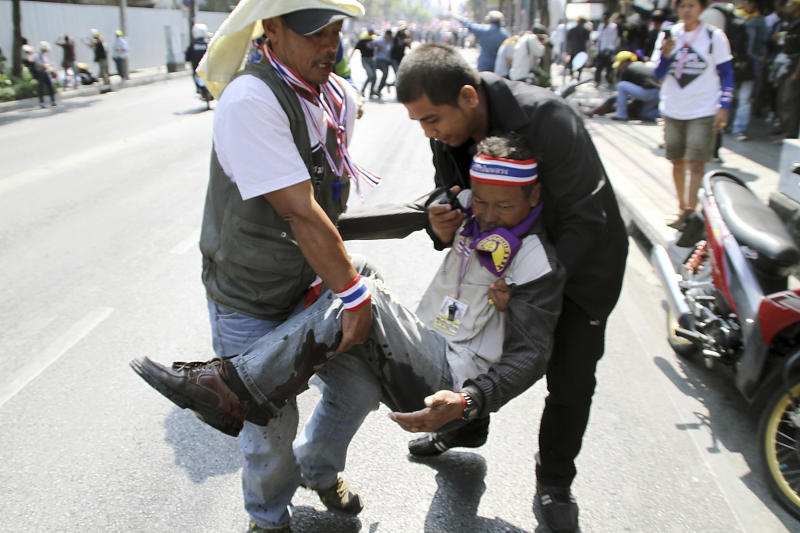 An injured anti-government protester is helped by his fellow protesters after he was hit by a bomb blast during the march with leader Suthep Thaugsuban in downtown Bangkok, Thailand Friday, Jan. 17, 2014. Dozens of people were wounded in Thailand's capital Friday when an explosion hit anti-government demonstrators marching through Bangkok in some of the bloodiest violence reported this year. (AP Photo/Daily News) THAILAND OUT