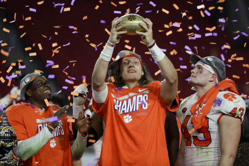 Clemson quarterback Trevor Lawrence holds the trophy after Clemson defeated Ohio State 29-23 in the Fiesta Bowl NCAA college football playoff semifinal Saturday, Dec. 28, 2019, in Glendale, Ariz. (AP Photo/Rick Scuteri)