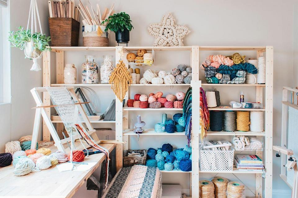"""<p>If your craft room is dedicated to weaving and/or knitting materials, take note of this workshop belonging to artist Lindsey Campbell, who runs the weaving-centric blog <a href=""""https://www.hellohydrangea.com/"""" rel=""""nofollow noopener"""" target=""""_blank"""" data-ylk=""""slk:Hello Hydrangea"""" class=""""link rapid-noclick-resp"""">Hello Hydrangea</a>. Keep all your things easily accessible with a modular wall shelving unit so all crafting materials (yarn, rope, winders, and more) stays organized. Then use glass jars to host remnants for recycling and baskets to assist with organization. </p>"""