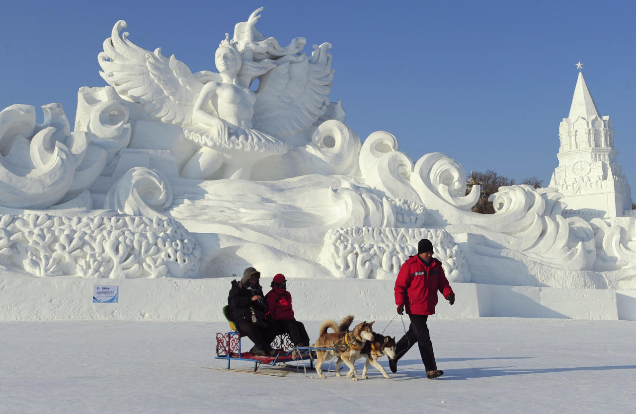 An employee pulls a dog sled carrying tourists in front of a snow sculpture ahead of the 13th Harbin Ice and Snow World in Harbin, Heilongjiang province December 26, 2011. The Harbin International Ice and Snow Festival will be officially launched on January 5, 2012. REUTERS/Sheng Li (CHINA - Tags: ENVIRONMENT SOCIETY ANIMALS TPX IMAGES OF THE DAY)