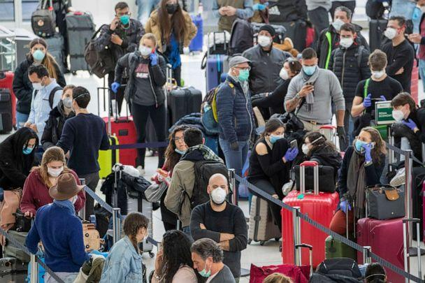 PHOTO: Passengers wear face masks to fend off coronavirus as they wait in line to check in for their flights, March 24, 2020, at JFK airport in New York. (Mary Altaffer/AP)