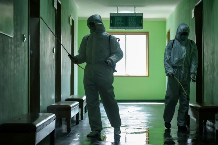 Health officials disinfect a corridor at the Pyongchon District People's Hospital in Pyongyang