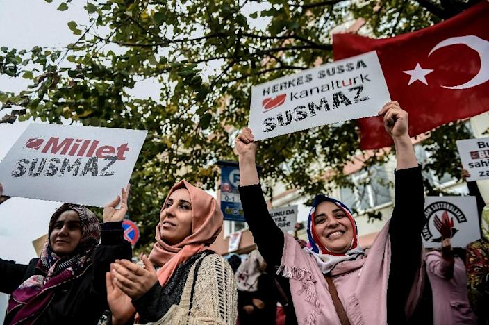 """Supporters of Bugun Newspaper and Kanalturk hold signs reading """"People won't be silent"""" during a protest in Istanbul against the Turkish government's crackdown on media outlets on October 27, 2015 (AFP Photo/Ozan Kose)"""