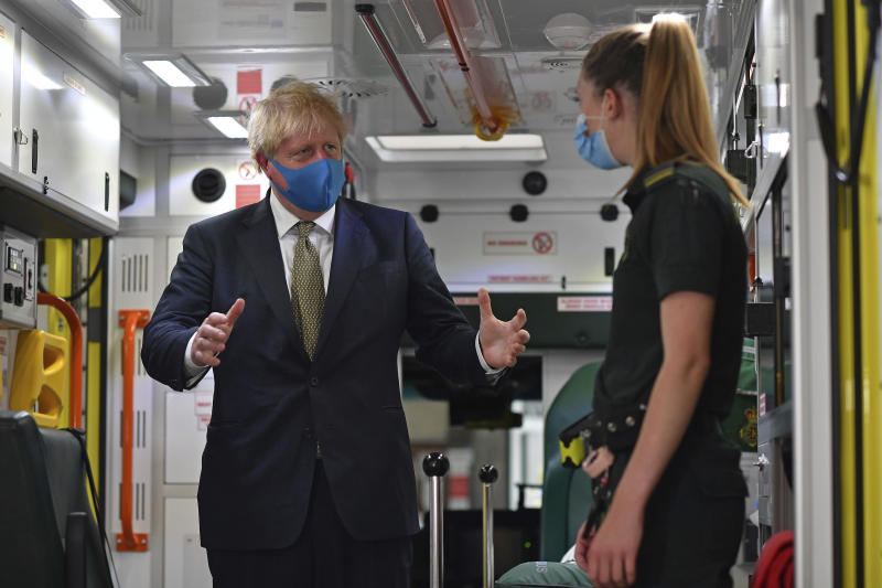 Britain's Prime Minister Boris Johnson, wearing a face mask, talks with a paramedic as they stand inside the back of an ambulance during a visit to the headquarters of the London Ambulance Service NHS Trust in London, Monday July 13, 2020. (Ben Stansall/Pool via AP)