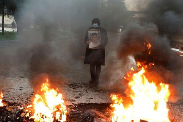 A woman holds a picture of one of the blast's victims during a protest earlier this year (Photo: Mohamed Azakir via REUTERS)