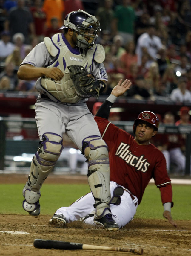 Colorado Rockies catcher Wilin Rosario , left, gets the force-out while avoiding Arizona Diamondbacks' Xavier Paul, right,in the ninth inning during a baseball game, Sunday, Aug. 10, 2014, in Phoenix. (AP Photo/Rick Scuteri)