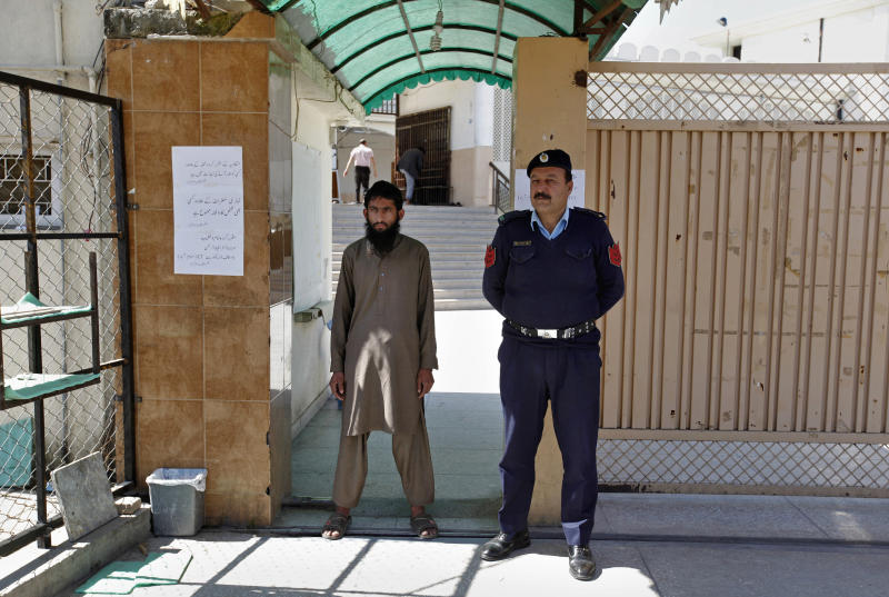 A Pakistani police officer stands guard with a worker of a religious group at the entrance to a mosque in Islamabad, Pakistan, Wednesday, March 6, 2019. Pakistan on Wednesday continued a crackdown on seminaries, mosques and hospitals belonging to outlawed groups, saying the actions were part of the government efforts aimed at fighting terrorism, extremism and militancy. (AP Photo/Anjum Naveed)