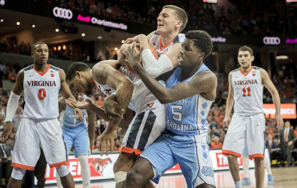 FILE - In this Jan. 6, 2018, file photo, Virginia's Kyle Guy, top, grabs rebound in front of Carolina's Jalek Felton (5) during first half of an NCAA college basketball game in Charlottesville, Va. The Cavaliers lead the nation in scoring defense, allowing 52.7 points per game. (AP Photo/ Lee Luther Jr.)