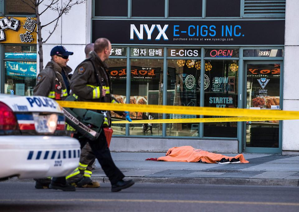 <p>A body lies covered on the sidewalk in Toronto after a van mounted a sidewalk crashing into a number of pedestrians on Monday, April 23, 2018. THE CANADIAN PRESS/Aaron Vincent Elkaim </p>