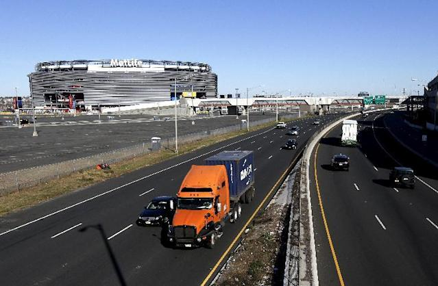"""In this photo taken on Wednesday, Nov. 13, 2013, traffic flows on a highway adjacent to MetLife Stadium in East Rutherford, N.J. Northern New Jersey towns hoping to get Super Bowl visitors to spend time and money in the Garden State and not just across the river in Manhattan, realize they need to come up with a creative game plan to separate itself from New York. There's a catch: None of the festivities can employ the words """"Super Bowl,"""" a name that is trademarked by the NFL. (AP Photo/Julio Cortez)"""