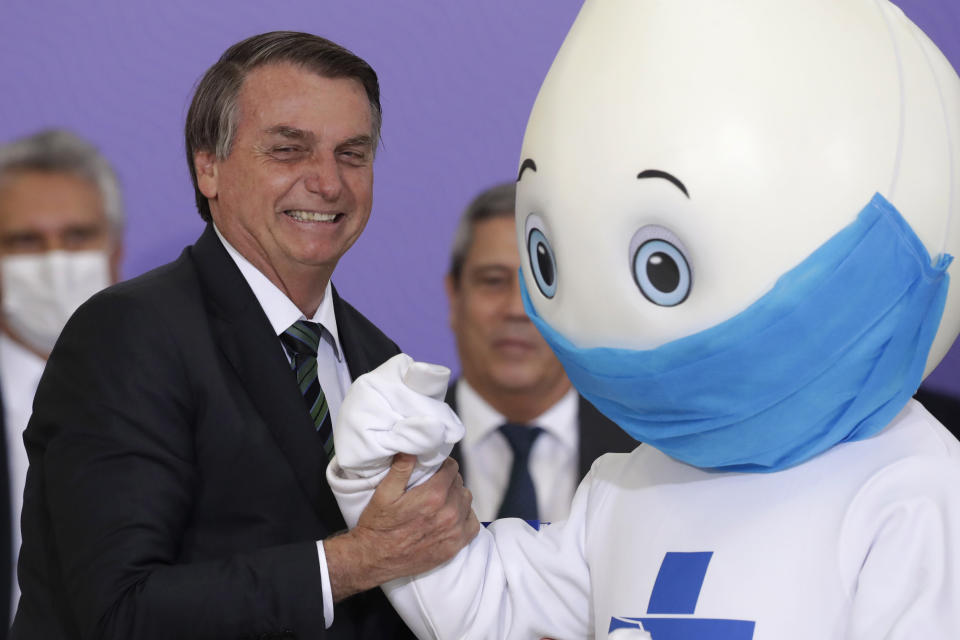"""Brazilan President Jair Bolsonaro poses for photos with the mascot of his nation's vaccination campaign, named """"Ze Gotinha,"""" or Joseph Droplet, during a ceremony to present the National Vaccination Plan Against COVID-19 at Planalto presidential palace in Brasilia, Brazil, Wednesday, Dec. 16, 2020. (AP Photo/Eraldo Peres)"""