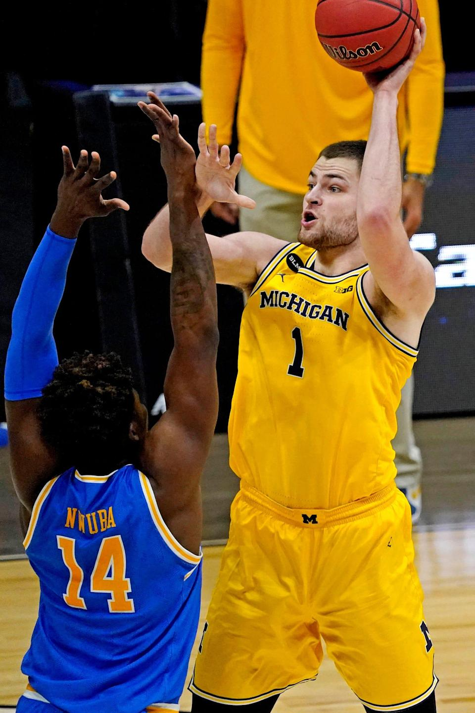 Michigan center Hunter Dickinson shoots the ball against UCLA forward Kenneth Nwuba during the second half of the Elite Eight game in the NCAA tournament on Tuesday, March 30, 2021, in Indianapolis.
