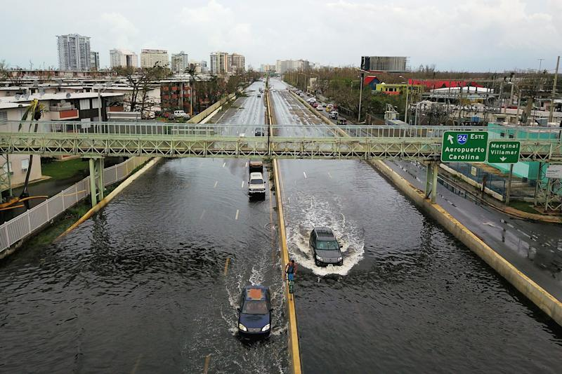 Cars drive through a flooded road in the aftermath of Hurricane Maria in San Juan on Sept.21, 2017. (RICARDO ARDUENGO via Getty Images)