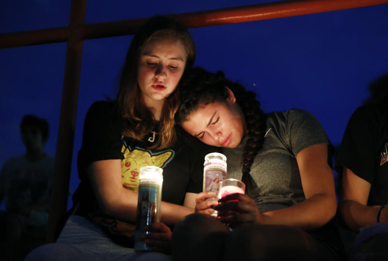 Melody Stout and Hannah Payan comfort each other during a vigil for victims of the shooting that occurred earlier in the day at a shopping center, Saturday, Aug. 3, 2019, in El Paso, Texas. (AP Photo/John Locher)