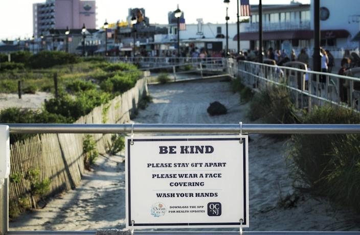 A sign along the boardwalk asks people to maintain social distancing and wear a face mask.