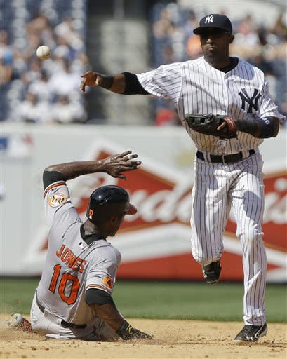 New York Yankees' Eduardo Nunez throws out Baltimore Orioles' Brian Roberts at first base after forcing out Adam Jones (10) at second base on a double play during the eighth inning of a baseball game Saturday, July 6, 2013, in New York. (AP Photo/Frank Franklin II)