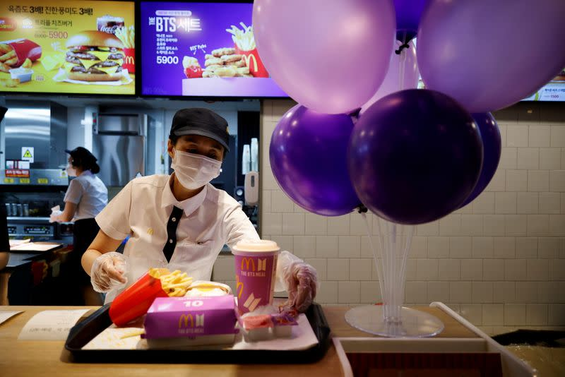 FILE PHOTO: An employee of McDonald's serves a BTS meal, which is inspired and promoted by K-pop boy band BTS, during lunch hour at its restaurant in Seoul