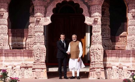 India's Prime Minister Narendra Modi shakes hands with French President Emmanuel Macron as he arrives to attend the International Solar Alliance Founding Conference in New Delhi