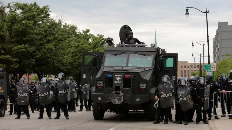 Detroit police, wearing riot gear, line up next to an armored vehicle in preparation to enforce a curfew following a rally against the death in Minneapolis police custody of George Floyd, in Detroit