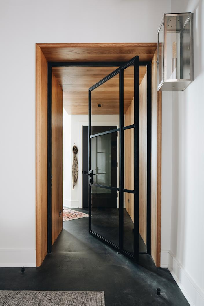"""<div class=""""caption""""> A glass door with a metal frame lets light in. </div>"""