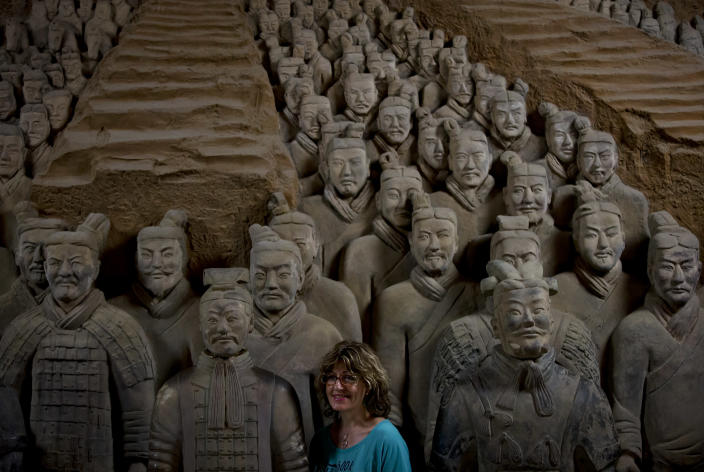 "In this Tuesday, July 30, 2013 photo, a foreign tourist stands near a terracotta warrior replica as she poses for a photo at the Museum of Qin Terracotta Warriors and Horses in Xi'an, in central China's Shaanxi province. China's new tourism slogan ""Beautiful China"" has been criticized by industry experts who say it illustrates a marketing problem that has led to a weakness in growth in foreign visitors over the past few years. (AP Photo/Andy Wong)"