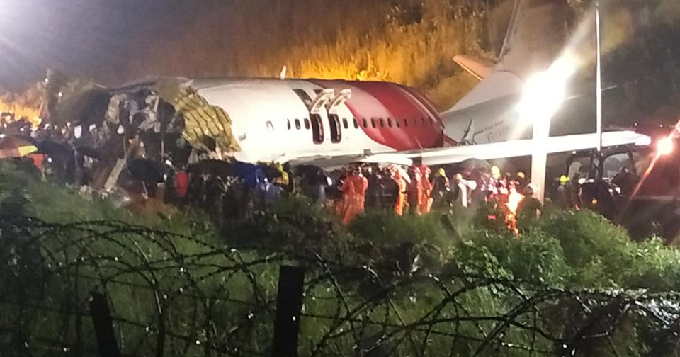 First responders gather around the wreckage of an Air India Express jet, which was carrying more than 190 passengers and crew from Dubai, after it crashed by overshooting the runway at Calicut International Airport in Karipur, Kerala, on August 7, 2020. - At least 19 people died when a passenger jet skidded off the runway after landing in heavy rain in India. (Photo by - / AFP) (Photo by -/AFP via Getty Images)