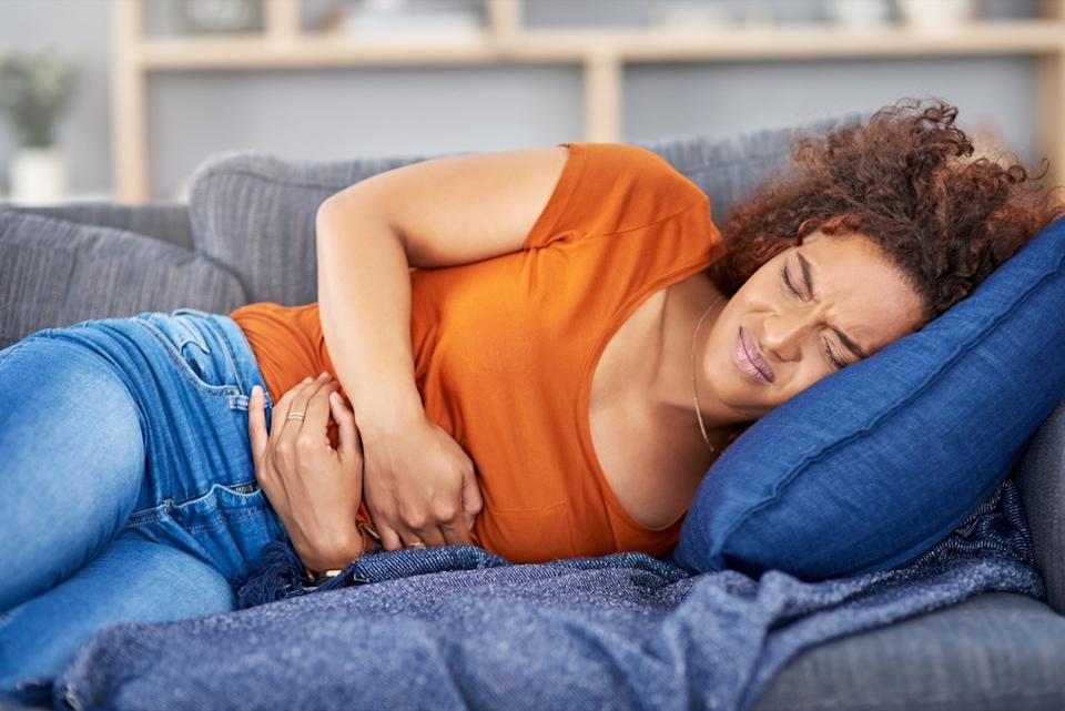 young black woman clutching her stomach in pain while lying on the couch