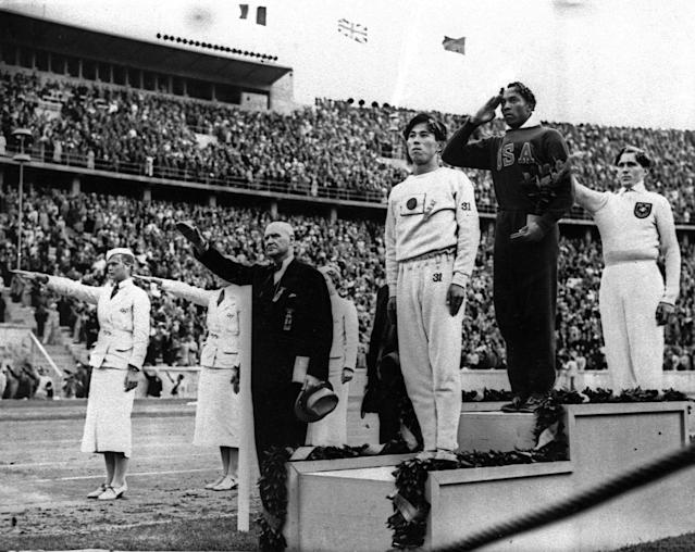 Olympic broad jump medalists salute during the medals ceremony Aug. 11, 1936 at the Summer Olympics in Berlin. From left on podium are: bronze medalist Jajima of Japan, gold medalist Jesse Owens of the United States and silver medalist Lutz Long of Germany. Long and German Olympic officials give the Nazi salute, while Owens gives a traditional salute. (AP Photo)